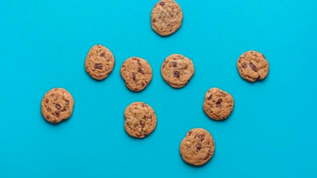 Chocolate chip cookies animation. Cookies moving on blue background Chocolate chip cookies moving on a blue seamless background. Cookies funny stop motion. Animated chocolate cookies. Home-baked sweet snacks 4k video. cookie stock videos & royalty-free footage