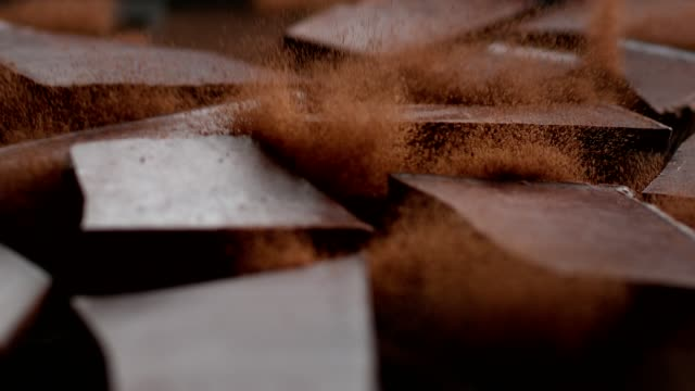 Chocolate cubes cracking on cacao powder. Cocoa explosions