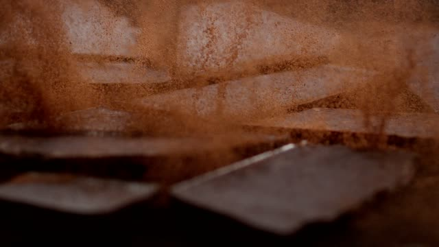 chocolate cubes cracking on cacao powder. cocoa explosions - cioccolato video stock e b–roll