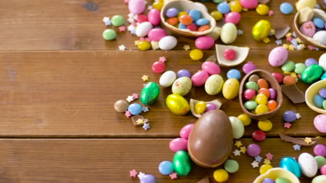 chocolate easter eggs and drop candies on table - pasqua video stock e b–roll