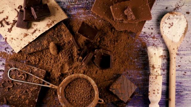 vídeos de stock e filmes b-roll de chocolate falls down on cocoa powder. slow mo. top view - cacau em pó