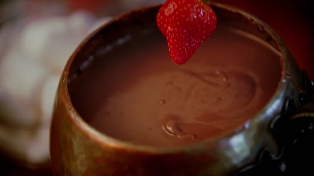 chocolate fondue in a pot served with fruits - immergere video stock e b–roll
