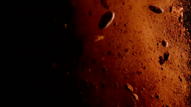 vídeos de stock e filmes b-roll de chocolate food explosion with cocoa powder, chocolate chips and nuts - cacau em pó