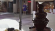 istock Chocolate fountain on table and people in interior of wedding hall 1195980679