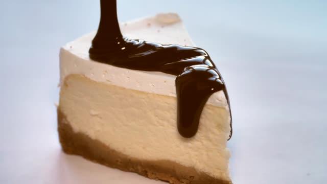 chocolate glaze pouring on dessert. close up of cheesecake decoration. - sernik filmów i materiałów b-roll