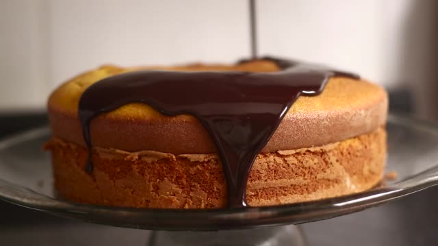 vídeos de stock e filmes b-roll de chocolate icing on carrot cake. - bolos