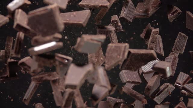 vídeos de stock, filmes e b-roll de explosão de peças de chocolate. câmera lenta 500fps - chocolate