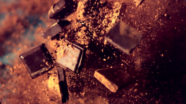Chocolate pieces falling down Chocolate pieces and cocoa powder falling down. Super slow motion. Close up. Camera trajectory control by fast robot arm. indulgence stock videos & royalty-free footage