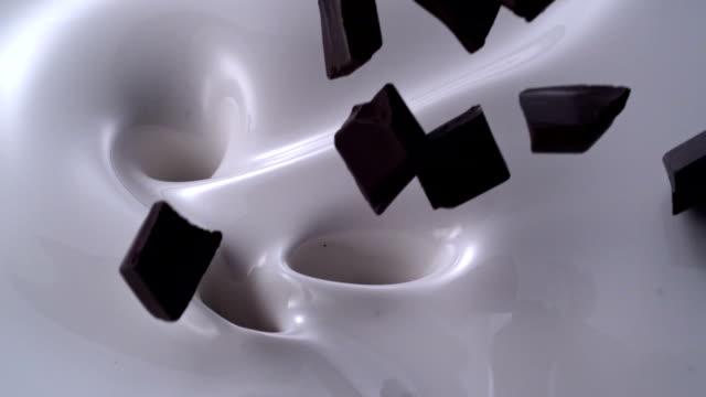 stockvideo's en b-roll-footage met chocolade stukjes die in een romige melk swirl vallen - milkshake