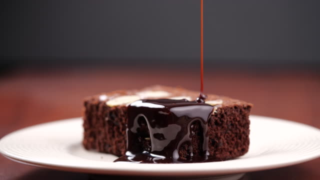 Chocolate pouring on cake in 4K Resolution. Topping chocolate on homemade brownie dessert