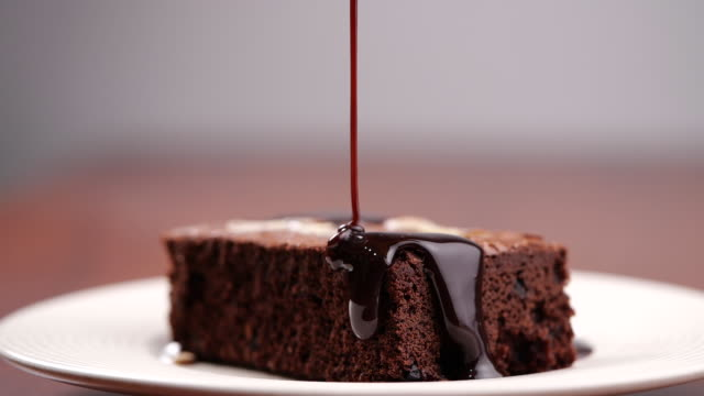 Chocolate pouring on cake in slow motion. Topping chocolate on homemade brownie dessert