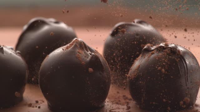 vídeos de stock e filmes b-roll de chocolate powder falling onto truffles in super slow motion. - cacau em pó