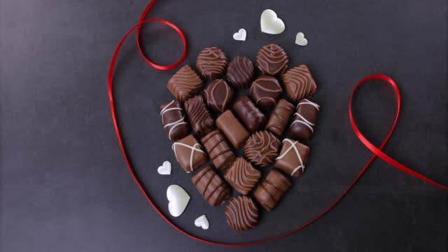 黒い背景に形作られたチョコレートプラリネのハート - バレンタイン チョコ点の映像素材/bロール