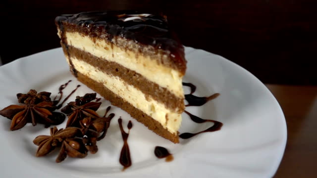Chocolate shaving, falling on a slice of cake, in slow motion at 500fps, rotating