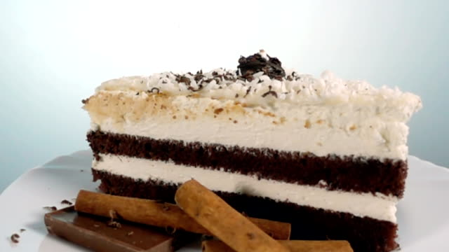 Chocolate shaving falling on a slice of cake, slow motion at 1000fps, rotating video