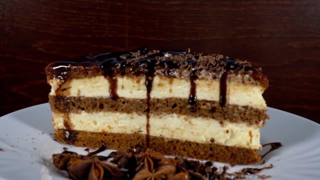 bir dilim pasta karşı ahşap döner, 4 k, çikolata şurubu dök - kek dilimi stok videoları ve detay görüntü çekimi