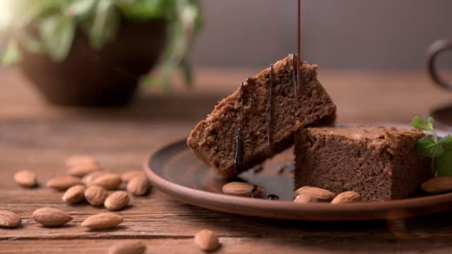 choklad topping hälla på hemmagjord choklad brownie. - brownie bildbanksvideor och videomaterial från bakom kulisserna