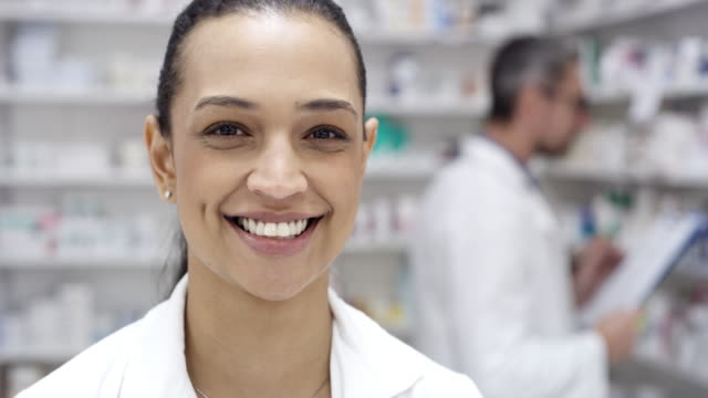 Choose us, because we put your wellbeing first 4k video footage of a young pharmacist working in a chemist with her colleague in the background pharmacist stock videos & royalty-free footage