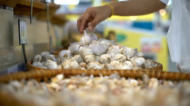 choosing garlic in supermarket close-up - aglio alliacee video stock e b–roll
