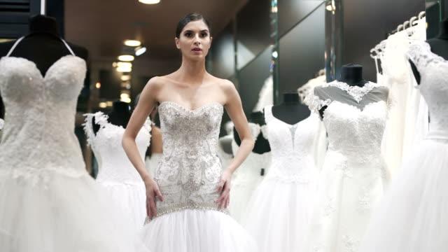 choosing her perfect wedding dress - modella negozio video stock e b–roll