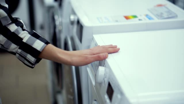 Choosing washing mashine in appliance store. Running hand by the row. Unrecognizable woman in household appliances department. Close up Choosing washing mashine in appliance store. Running hand by the row. Unrecognizable woman in household appliances department. Close up. electrical equipment stock videos & royalty-free footage