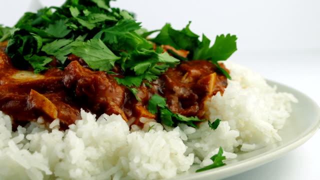 vídeos de stock e filmes b-roll de chopped coriander added to chicken tikka masala - meat plate