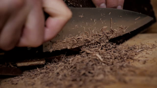 vídeos de stock e filmes b-roll de chopped dark chocolate on kitchen board. chopping a bar of chocolate while making baking. slow motion. close up. chop chocolate on cutting board on wooden table . closeup. - fruto do cacau