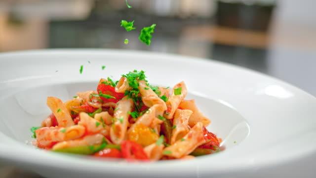 vídeos de stock e filmes b-roll de slo mo td chopped fresh parsley falling onto pasta - utensílio