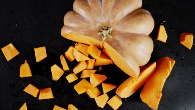 Chopped pumpkin rotates slowly. On a black background.