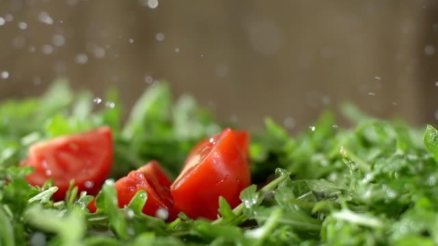slo mo chopped tomato falls on arugula - sallad bildbanksvideor och videomaterial från bakom kulisserna