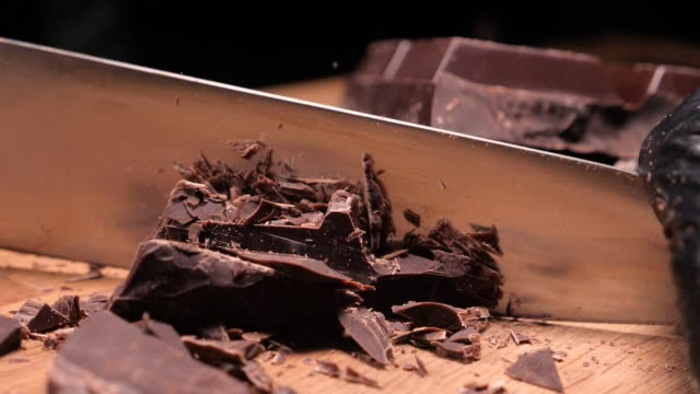 chopping chocolate on cutting board on wooden table as baking ingredient preparation (slow motion) - theobroma video stock e b–roll