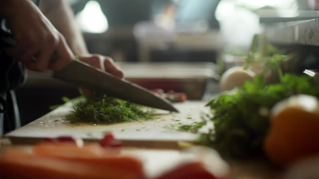 chopping herbs Stock vdeo clip, shot on a small dolly, of a chef preparing herbs & vegetables in a small restaurant. ingredient stock videos & royalty-free footage