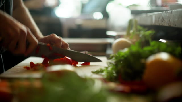 Chopping peppers in a restaurant Close up dolly clip of a professional chef cutting up a red bell pepper (capsicum) on a vegetable chopping board. ingredient stock videos & royalty-free footage