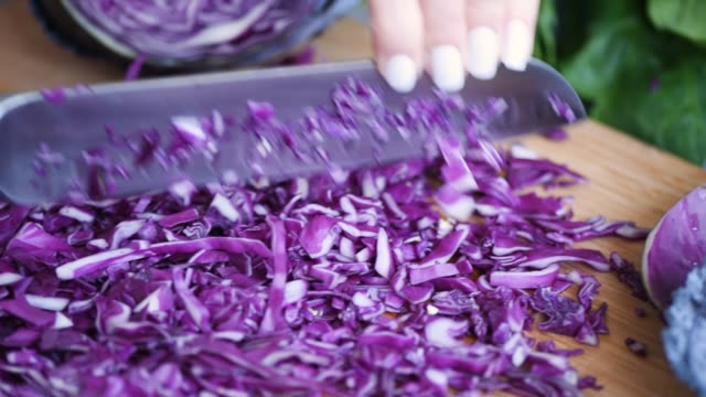 Chopping red cabbage Closeup view of chopping red cabbage on bamboo cutting board. Healthy vegan or vegetarian cooking cabbage stock videos & royalty-free footage
