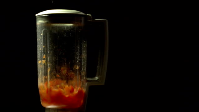 Chopping tomatoes in a blender on a black background, slow motion video