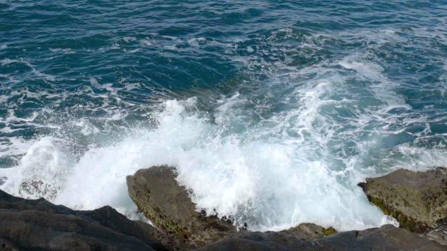 Choppy sea hitting rocky cliffs, breaking into foamy splashes, amazing nature video