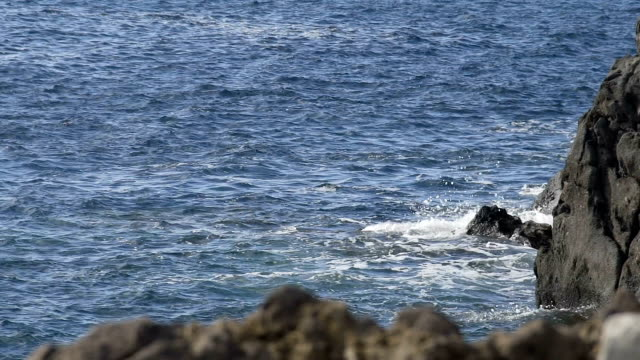 Choppy waves of blue sea hitting rocks, cliffs emerging from water, slow motion video