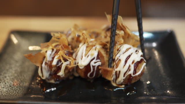 chopstick picking takoyaki, spuntino giapponese a forma di palla - antipasto video stock e b–roll