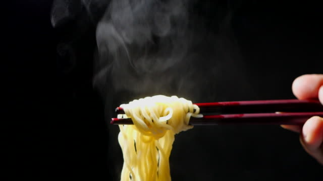 vídeos de stock e filmes b-roll de chopsticks to tasty noodles with steam and smoke on black background in slow motion, asian meal close-up, junk food and fast food concept - comida asiática