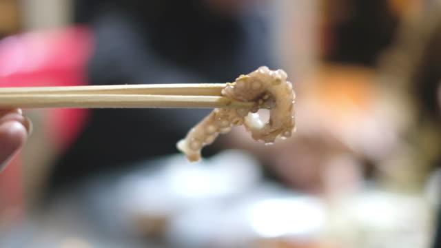 Chopsticks tong octopus tentacle. Famous korean food Chopsticks tong octopus tentacle in restaurant. Famous korean food style sashimi stock videos & royalty-free footage
