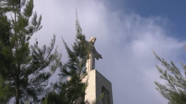 vídeos de stock e filmes b-roll de christ the king sanctuary behind branches - cristo rei lisboa