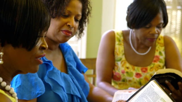 Christian women listening to scripture reading from the Bible Focus moves from a women listening and nodding with approval to her friend who is reading from the Holy Bible. Rack Focus Shot sister stock videos & royalty-free footage