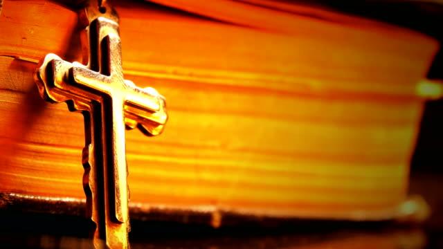 kristendomen cross bibeln och brand reflektion på cross - krucifix bildbanksvideor och videomaterial från bakom kulisserna