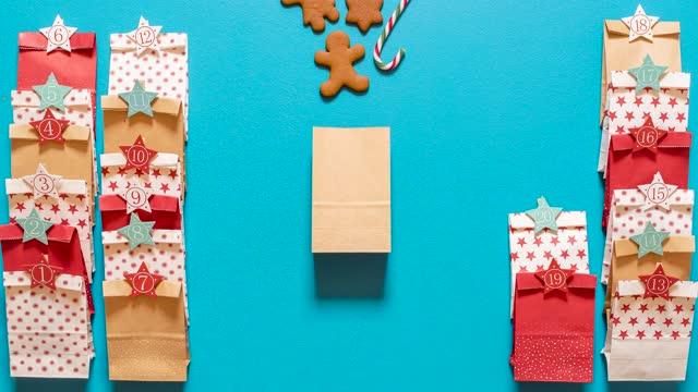 weihnachts-adventskalender stoppen bewegung. 24 geschenktüten mit keksen und zuckerstangen - advent stock-videos und b-roll-filmmaterial