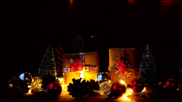 Christmas and New Year background with gifts. Presents wrapped in craft paper with holiday symbols - heart and fir tree. Snow is falling from above video