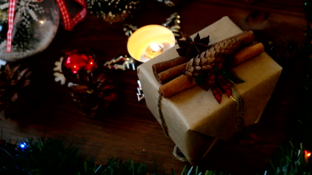 Christmas and New year background with presents, lights, candles and different decorations. Gift in craft paper with cinnamon video