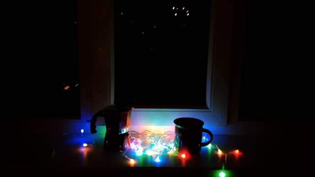 Christmas and New Year composition. Cup of coffee, red geyser coffee maker and lights on windowsill of the night. video