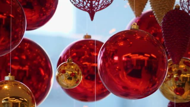 weihnachten und neujahr dekoration. weihnachten große rote kugeln auf hintergrund von leuchtenden laternen und gold girlanden. urlaub hintergrund. blinkende girlande. rote kugeln mit lichtern funkeln nahaufnahme. - girlande dekoration stock-videos und b-roll-filmmaterial