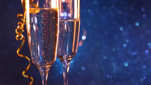 vidéos et rushes de fond de vacances de noël et de nouvel an avec deux goblet, champagne de verre de vin et fond bleu d'effet de bokeh. bonne année - flûte à champagne