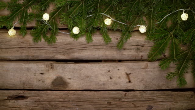Christmas background. Christmas tree branches with blinking garland on rough weathered wooden planks, with copy space